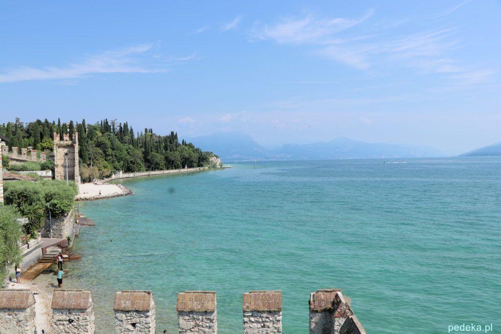 Mury zamkowe, brzeg jeziora i góry w tle