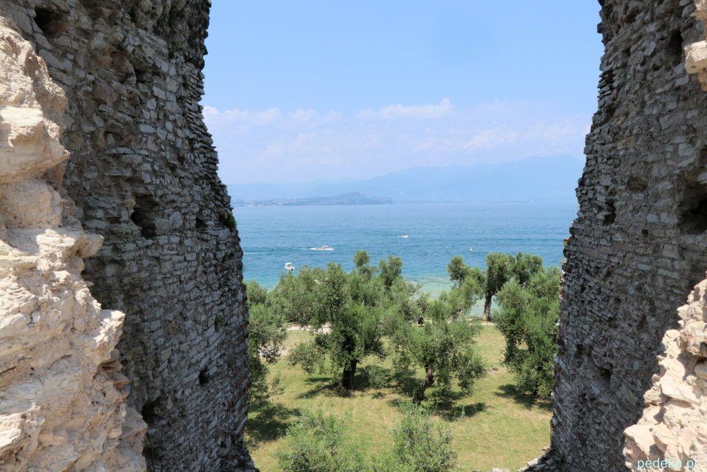 Okno w murze z widokiem na drzewa i jezioro