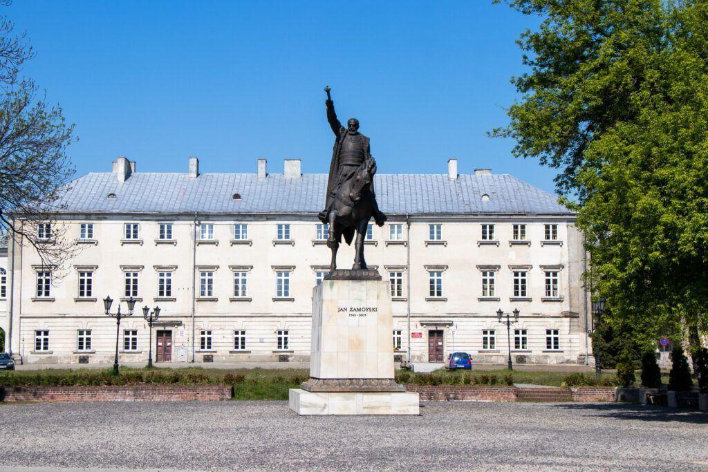 Jeden dzień w Zamościu. Pomnik Jana Zamoyskiego, a za nim pałac