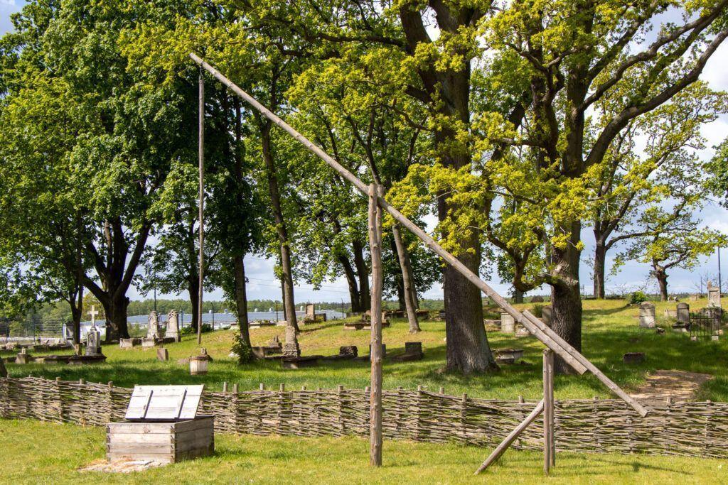 Olenderski Park Etnograficzny. Żuraw, a za nim cmentarz